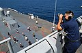 US Navy 030223-N-0000X-002 Sailor stands watch as the forward lookout watch while his shipmates from all the branches of the military play volleyball on the main deck during a Steel Beach Picnic.jpg