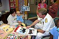 US Navy 050926-N-7163S-004 A mother and her two year old daughter listen with interest at the Minneapolis Children's Hospital, while Director of Surface Warfare, Rear Adm. Barry McCullough, discusses the Navy's mission.jpg