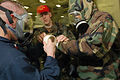 US Navy 060819-N-3946H-169 Damage Control Training Team members help a Sailor don toxicological gloves over his chemical protective suit.jpg