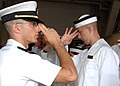 US Navy 070627-N-1026O-003 An upperclass midshipman teaches a plebe, or freshman, from the U.S. Naval Academy Class of 2011 to properly wear the plebe cover.jpg