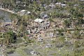 US Navy 071120-M-8966H-007 An aerial view reveals toppled trees and debris scattered throughout an affected village.jpg
