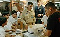 US Navy 080619-N-9533G-160 Lt. Joseph W. Cortopassi, center, the Air Boss aboard the amphibious transport dock ship USS Dubuque (LPD 8), helps serve ice cream to students of the Dahil Model Independent School.jpg