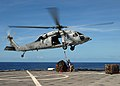 US Navy 080907-N-9134V-102 Boatswain's Mate 3rd Class Willy Holland and Lance Cpl. Christopher Marchewka hook a cargo net to an MH-60S Sea Hawk helicopter.jpg