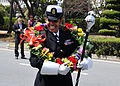 US Navy 110409-N-RO948-012 Chief Musician Lucliada Barbosa tries on a flower wreath as the U.S. 7th Fleet Band prepares to march in a street parade.jpg