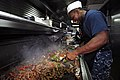 US Navy 110906-N-RC734-028 Culinary Specialist 2nd Class Sanford McCants prepares beef fajitas for the lunch meal aboard USS Comstock (LSD 45).jpg
