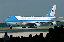 Presidential aircraft taxiing in front of silhouetted crowd.