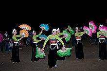 Seis mulheres fantasiadas, segurando leques em cada mão, dançam em frente ao público
