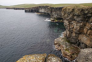 Westray - West coast of Westray Looking along the sandstone cliffs to the rock arch at Neven o'Grinni.