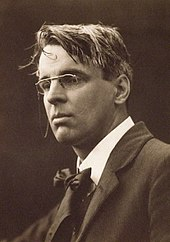 A posed black and white photograph of Yeats. He is wearing smart clothes and spectacles, while his hair looks a bit tousled