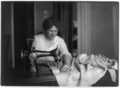 Woman sewing with a Singer sewing machine.png