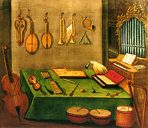 Musicology - Late 18th-century painting of instruments from the school of Zlatá Koruna. On the wall are several lutes and brass instruments. On the left is a cello-type instrument. In the middle are several drums. On the right is a small pipe organ.
