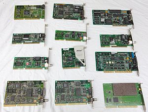 Network interface controller - 12 early ISA 8 bit and 16 bit PC network cards. The lower right-most card is an early wireless network card, and the central card with partial beige plastic cover is a PSTN modem.