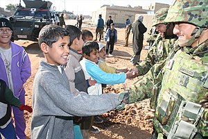 Japanese Iraq Reconstruction and Support Group - Iraqi children shake hands with JGSDF soldiers during a reconstruction operation.