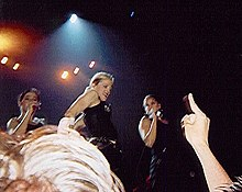 Right profile of a blond woman, flanked by two other woman who are singing in a microphone. The blond woman wears a black t-shirt and her hair is tied in a bun. Behind them, lights flash from above. The hand and head of a person is visible below.