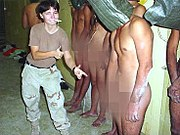 "Spc. Lynndie England signals a ""thumbs up"" sign and points at a hooded, naked Iraqi prisoner."