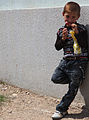 A local child in the town of Al Koosh eats candy as he watches his older brother play catch with U.S. Soldiers from 214th Military Police Company in the northern town of Al Koosh, Iraq, May 3, 2011 110503-A-RH393-330.jpg