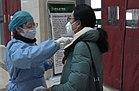 Pielęgniarka mierząca temperaturę ciała dla pacjentów ambulatoryjnych w Hubei TCM Hospital.jpg