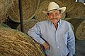 A producer stands next to his hay crop for the year. (24745681219).jpg