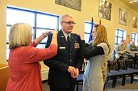 Air Force Col. John Flowers, center, the North Dakota National Guard Joint Force Headquarters chaplain, smiles as his wife, Debbie, left, and daughter, Sara, affix new rank to his uniform during a promotion 130117-Z-WA217-025.jpg