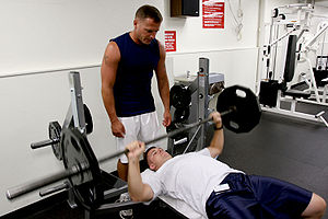 Bench press - A man performs a barbell bench press while another spots him.