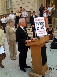 "Barr stands outside at a podium with the words ""U.S. and Iran: It's time to talk"" written on a poster standing upright in the front, surrounded by listeners"