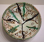 Bowl with prancing lion, Iran, Garrus district, Seljuk period, 12th or 13th century AD, earthenware with carved and painted slip design under transparent glaze with splashes - Cincinnati Art Museum - DSC03985.JPG