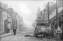 A soldier walks up a high street; the sides of the road are covered with rubble. In the foreground there is a knocked out tank, at the foot of the tank there is a dummy wooden gun barrel and debris. Another knocked out tank being examined by another solder occupies the background.
