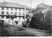 A black and white image of several buildings with Chinese-style wide-eaved roofs making a corner around a parking area where a 1920s-style automobile is parked