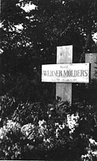 "Black-and-white photograph of a wooden cross on a grave, bearing the inscription ""Oberst Werner Mölders, 18. 3. 1913 – 22. 11. 1944."" The name Werner Mölders is in large letters. Trees are seen in the background; the area in front of the cross is covered with low-growing plants bearing flowers."