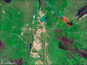 Catoca diamond mine - Satellite image of the mine from June 21st, 2001. The light red point in the north-east of the mine is a bush fire.