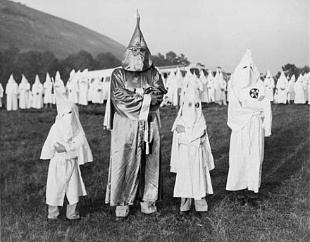 Two children wearing Ku Klux Klan robes and hoods stand on either side of Dr. Samuel Green, a Ku Klux Klan Grand Dragon, at Stone Mountain, Georgia on July 24, 1948. Children with Dr. Samuel Green, Ku Klux Klan Grand Dragon, July 24, 1948.jpg