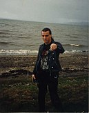 A man, Chuck Schuldiner, is shown on a dark shoreline. He has long hair, black pants and a black shirt, and a black leather jacket.