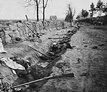 Trincea con fucili abbandonati e uomini morti
