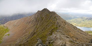 A sharp arête is seen obliquely; the sheer faces bear no vegetation and are made of noticeably reddish rock. Dozens of people can be seen clambering along the ridgeline.