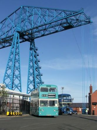 County Borough of Teesside - Preserved Teesside Municipal Transport L544, a 1972 Northern Counties bodied Daimler Fleetline CRL6, with Dennis Loline 99 in dark blue Middlesbrough Corporation livery at Middlesbrough Transporter Bridge.