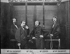 "Davenport brothers - This 1870 photograph shows the brothers and William Fay in front of the ""spirit cabinet""."
