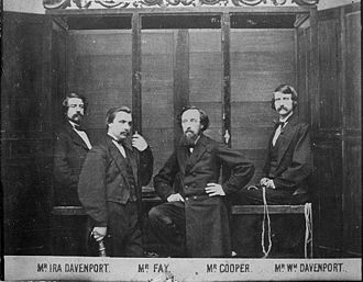 """Davenport brothers - This 1870 photograph shows the brothers and William Fay in front of the """"spirit cabinet""""."""