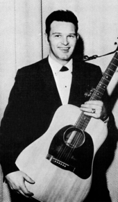 A dark-haired young man in a dark jacket, smiling broadly while holding a guitar