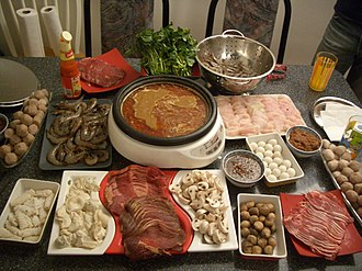 Hot pot - A common hotpot preparation: raw foods ready to be cooked, with hot broth at the center of the table.