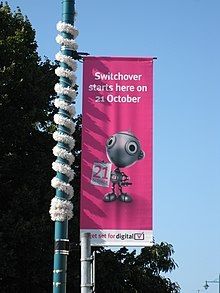 "Cifereca Ŝaltiltranspafstandardo kun teksto diranta ""Switchover starts here on 21 October"""