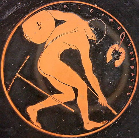 a Greek pentathlete with a mattock for preparing the skamma to the left (kylix painting c. 500 BC) – Greco-Roman Skamma (Wrestling Pit)