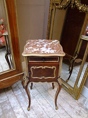Distressing - A table given an antiqued appearance resembling Florentine-style woodwork, with gold paint applied to carved details to resemble gold gilding.