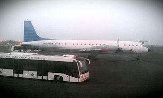 Transport in Djibouti - An Ilyushin Il-18 aircraft and ferrying bus on the Djibouti–Ambouli International Airport runway.