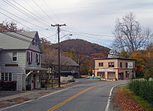 "A two-lane road curves from center bottom to center right. On the right is a gray house. Next to it is a darker gray, longer house, on a road that splits off from the one in the image. At the junction is a pale gold building with brown trim and a sign that reads ""Calsi's General Store"". A white building and hill are in the distance behind it. Some autumn color is visible on the trees."