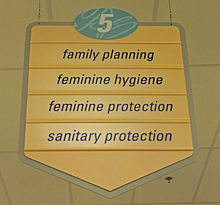 "A yellow sign with a pointed bottom. At the top is the number 5 in an oval with a blue background. Below it are the words ""family planning"", ""feminine hygiene"", ""feminine protection"" and ""sanitary protection"""