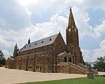 "The D.R. Church in Heidelberg, situated in HF Verwoerd Street, is one of the finest examples in Gauteng of a church built of stone. It is visible from all sides and is indeed a worthy monument. The corner-stone of the church was laid on 12 April 1890, Type of site: Church. The church was inaugurated in 1890. At a meeting held in the basement hall on 24 July 1903, it was decided to establish a ""Volkskool"". As a result of this, the present ""Hoër Volkskool"" and the Heidelberg Training College came into being."