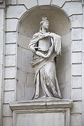 A photograph of a white statue of a woman clothed in a long robe looking to the right and placing her left hand on her chest in a white archway in a wall
