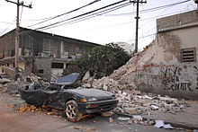 A deep green color car with its roof caved in and the back of the car crushed in. In the background, there is a tree, two phone line poles and a wall with graffiti on it that is half broken down.