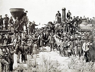 The Golden Spike where the First Transcontinental Railroad was completed in the U.S. on May 10, 1869, in Promontory, Utah East west shaking hands by russell.jpg