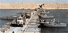 Military trucks crossing a canal on a pontoon bridge